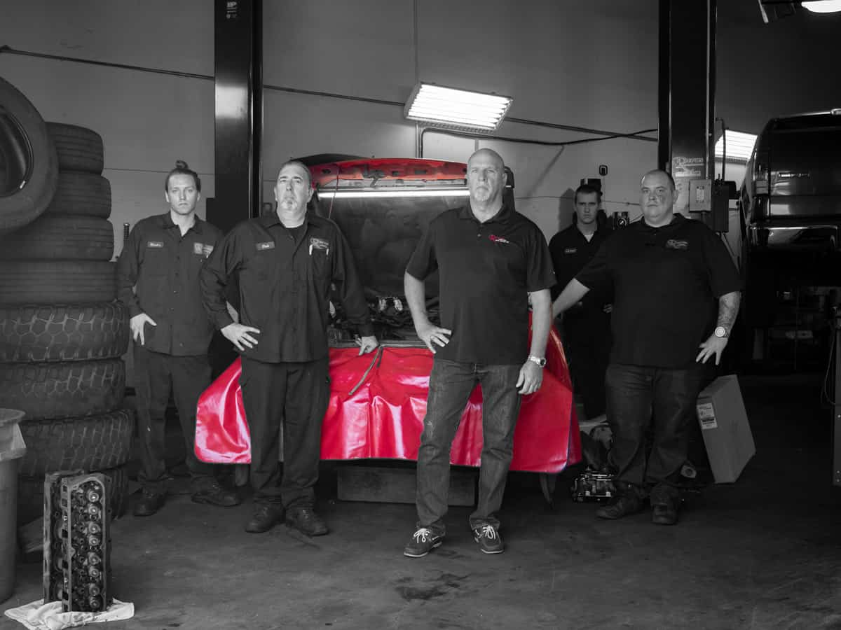 Reeves Team posing in front of vehicle in shop