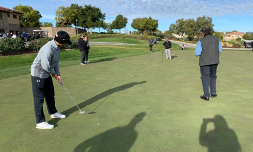 People observing a contestant putting in the 2019 Reeves Complete Auto Center golf tournament