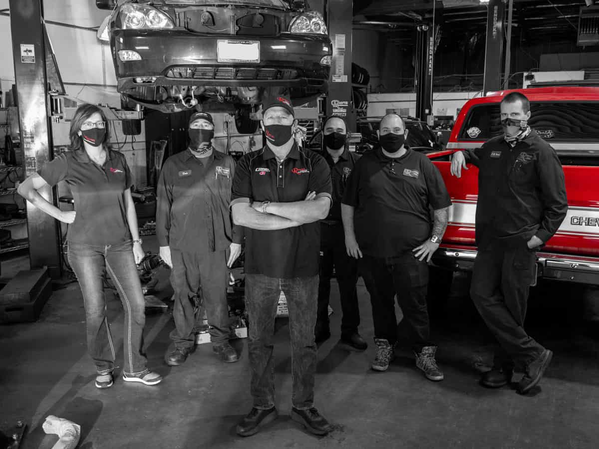 Reeves Team posing while wearing face coverings in front of vehicles in shop