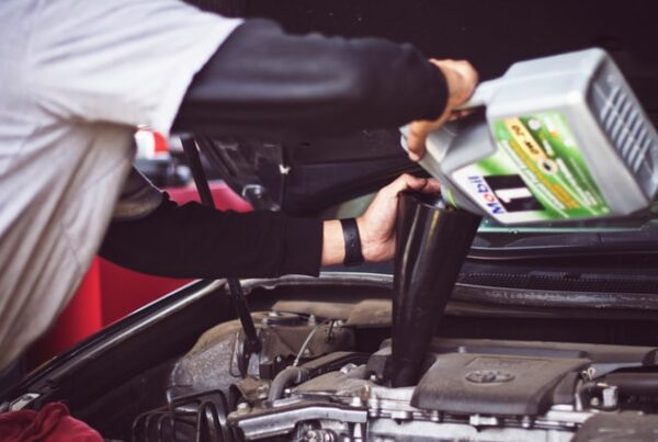 Man pouring motor oil into engine as part of a routine oil change
